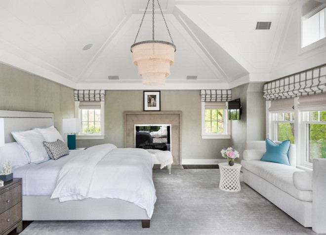 Neutral bedroom with vaulted ceiling accented with a 3 tier linen chandelier illuminating a light gray nailhead bed flanked by wood 2 drawer nightstands and turquoise blue lamps facing a white chaise lounge lined with turquoise blue velvet pillows. Chic bedroom boasts a textured gray wall accented with taupe stone fireplace alongside a white bench flanked by windows dressed in gray striped roman shades. Alisberg Parker Architects.