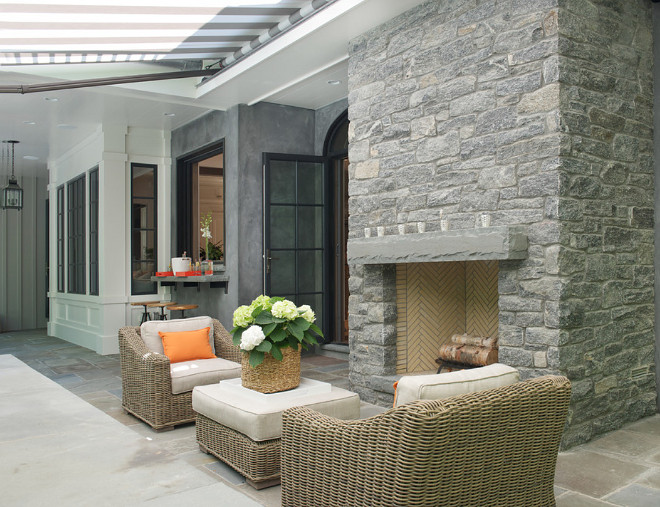 Outdoor Stone Fireplace and stone patio. Stone fireplace is Byram black fieldstone. The stone patio floor tiles is bluestone