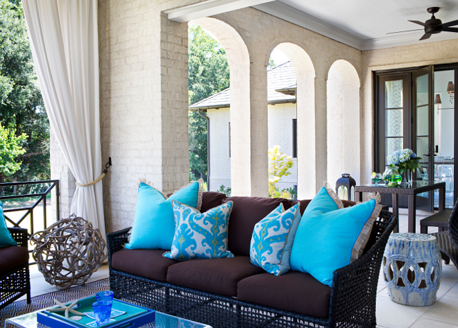 Porch. Back porch. The back porch features off-white brick walls and columns accented with white outdoor curtains. Notice the chocolate brown rattan sofa with brown cushions, turquoise ikat pillows and turquoise blue pillows. #porch #backporch TS Adams Studio Architects. Traci Rhoads Interiors.