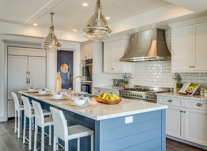 Three paint colors used in the kitchen. Gray lower cabinets and fridge panels paint color is Benjamin Moore Nimbus. White upper cabinets paint color is Benjamin Moore White Dove. Blue island paint color is Benjamin MooreEvening Dove. #Kitchen #paintcolors Titan & Co