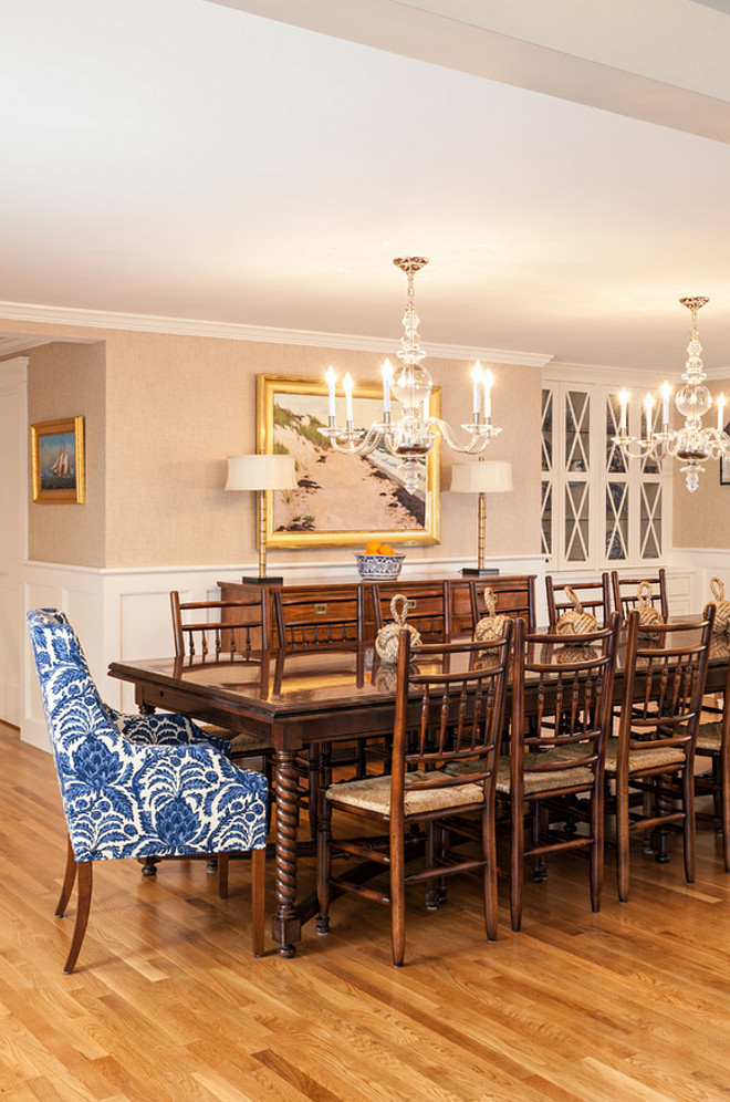 Traditional dining room with a twist. I love the traditional wainscoting, the wallpaper and the double chandeliers. The walls in the dining room are covered in grasscloth by Ralph Lauren. The chandeliers are from Visual Comfort and are even prettier in person. The fabric on the host and hostess chairs is Brunschwig & Fils Bromelia Resist in Blue. The Marcy Armchair is from Kravet and can be ordered in any fabric. Table is custom from Kravet and side chairs are from a consignment shop. #diningroom #traditionalDiningroom #diningroom #chandeliers #furniture Violandi + Warner Interiors