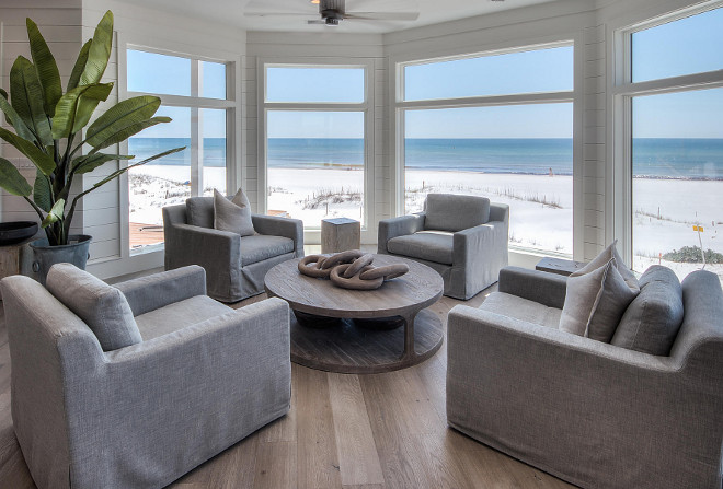 Transitional Coastal Interiors. Just off the living room, a sitting area is nestled in front of a gallery of bay windows. Beach house with Transitional Coastal Interiors. Beach house with transitional coastal interiors, with whitewashed plank hardwood floors, slipcovered furniture, reclaimed furniture and tongue and groove walls. #TransitionaInteriors #Interiors #CoastalInteriors