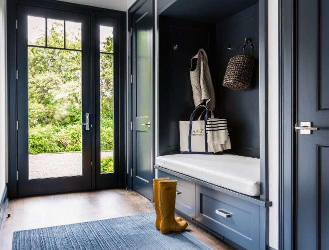 Dark Blue Mudroom. Dark blue mudroom features a dark blue built in bench fitted with drawers placed under a dark blue backsplash lined with hooks flanked by dark blue closet doors. #Mudroom #darkblue #navy Alisberg Parker