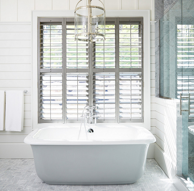 Bathroom Window Shutter Ideas. Bathroom features a Round Edwardian Entry lantern suspended over a freestanding tub placed under windows dressed in plantation shutters alongside a grey marble tiled floor next to a shiplap and glass walk in shower. Muskoka Living