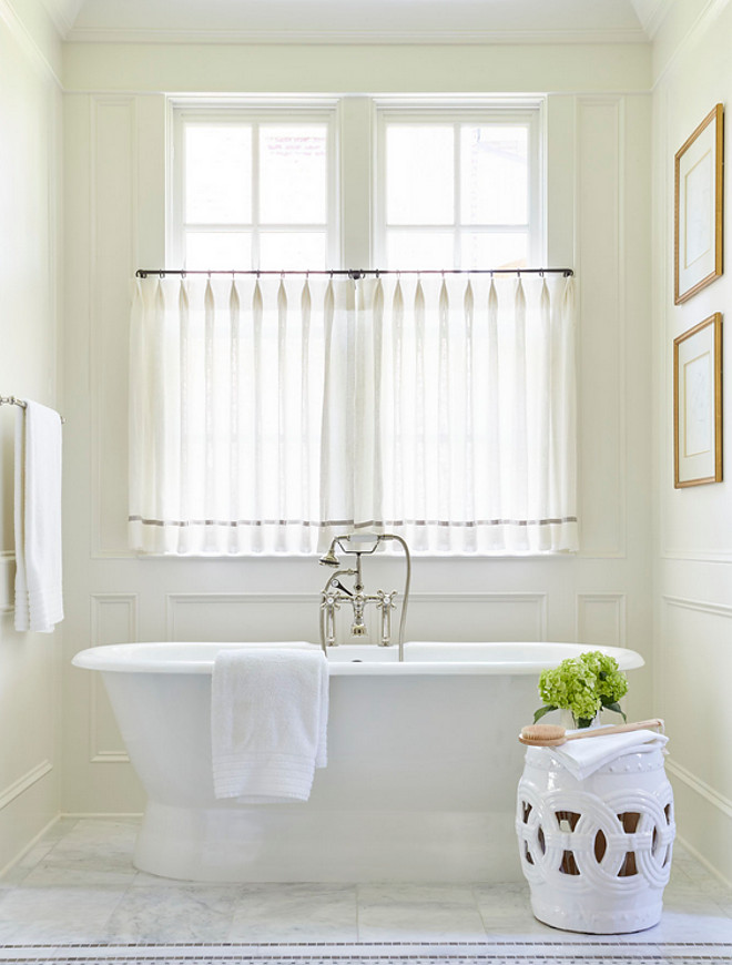 Bath nook wainscotting. Bath nook is clad in decorative wall moldings filled with a roll top tub and a vintage hand held tub filler as well as a white rope stool placed under windows dressed in white sheer cafe curtains accented with gray trim. #bathnook #nook #wainscotting Sarah Bartholomew Design