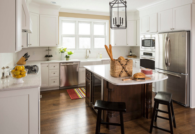 Traditional white kitchen with dark stained kitchen island. Cabinets are painted in White Dove by Benjamin Moore and Walls are painted in Benjamin Moore Shaker Beige. Traditional kitchen. #Kitchen #TradtionalKitchen #StainedIsland Renae Keller Interior Design, Inc.