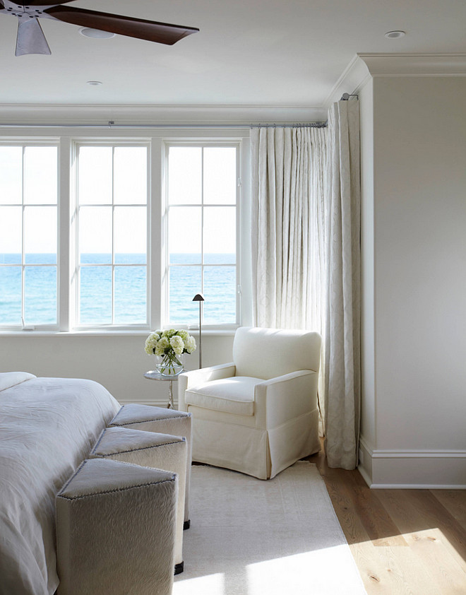 White Bedroom. White bedroom with ocean view. White bedroom with ivory white walls, ivory white draperies and white slipcovered bedding and white bedding. #Whitebedroom #ivorywhitebedroom #white #bedroom #interiors