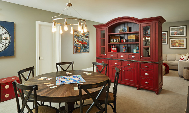 Basement Ideas. Smart Basement Ideas. Basement Design Ideas. Red Cabinet in basement is custom by Benchmark Wood Studio and is a two sided piece with TV on one side and shelving on the other. Serves as a buffer to the game space and lounging area. #BasementIdeas #Basementdesignideas #Basements