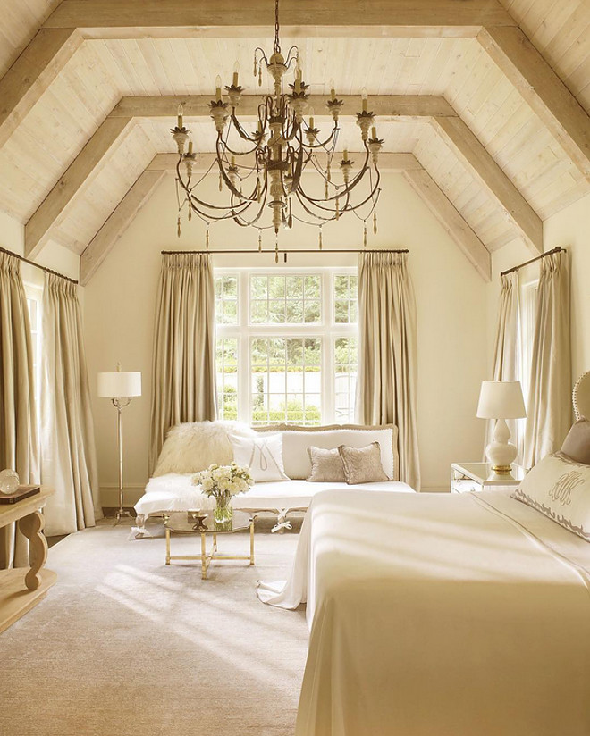 A vaulted oak ceiling and antique chandelier give this bedroom, designed by Suzanne Kasler, a warm feel.