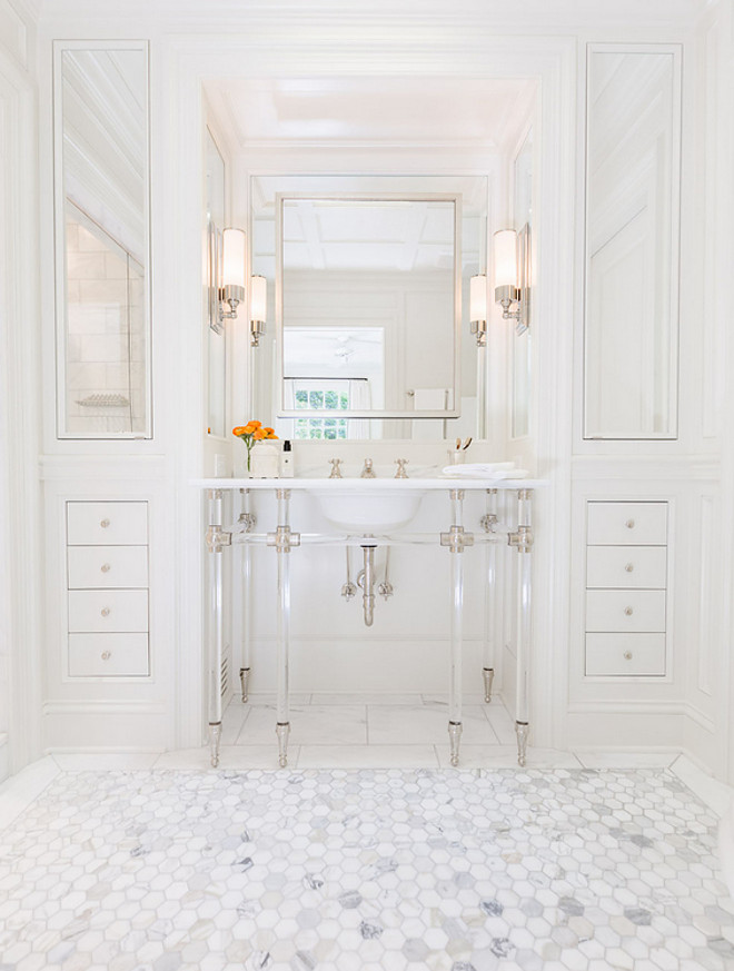 Bathroom washstand. Bathroom washstand. Bathroom features a 6 leg nickel and glass washstand topped with marble placed under a satin nickel mirror flanked by floor to ceiling built in cabinets accented with mirrored cabinet doors alongside a marble hexagon tile floor. #Bathroomwashstand #bathroom #washstand Sarah Bartholomew Design