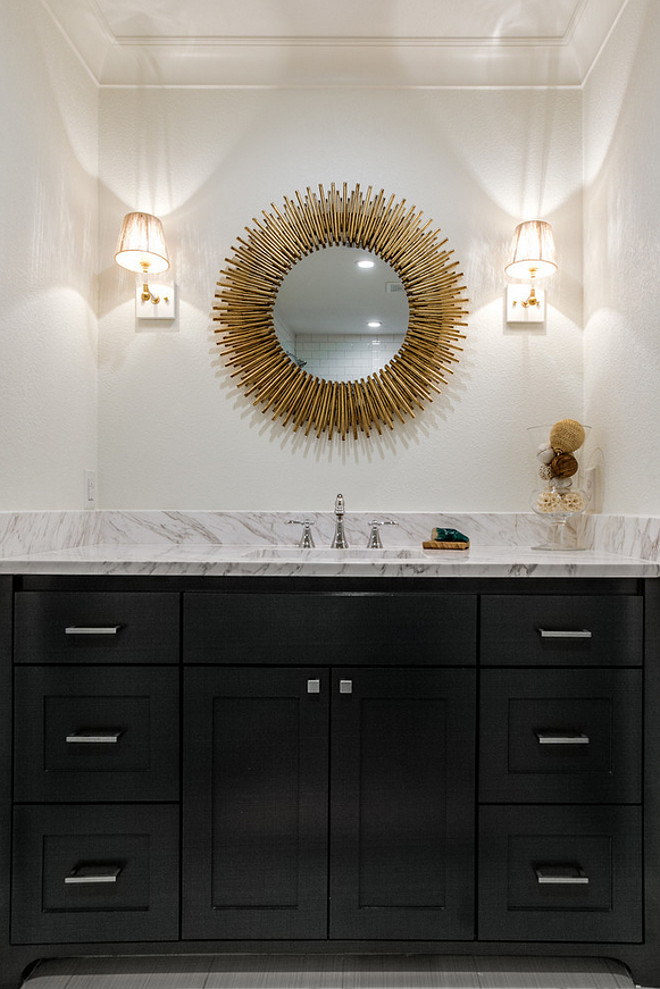 Bathroom with black cabinetry, brass mirror and brass lighting. The countertop is a Volakas 3cm polished marble slab. Mirror is from Arteriors Home - the Prescott Round Mirror. #Bathroom #Brassmirror #mirror #lighting #bathroomlighting Redo