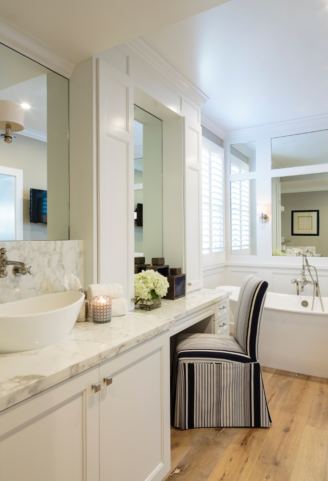 Bathroom. Bathroom with hardwood floors. Small Bathroom with hardwood flooring and white cabinetry. The master bathroom has a serene and organic feel thanks to the white cabinetry, marble counters and wide hardwood floors. #Bathroom #hardwoodfloors Designed by Barclay Butera.
