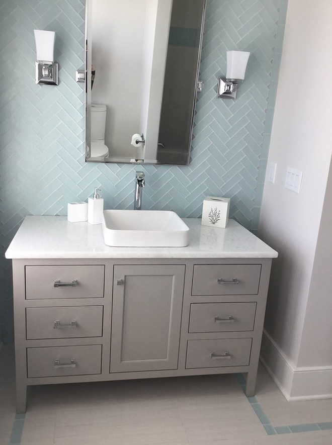 Bathroom. This bathroom features floor-to-ceiling subway tile in a herringbone pattern. The vanity is painted vanity in a soft gray - Sherwin Williams SW7023 Requisite Gray. Subway tile is in a herringbone pattern. Painted vanity in a soft gray. Walls: Sherwin Williams Anew Gray & 3x6 Capricco sky blue glass tile in 3x6 herringbone pattern. Countertop is Silestone Quartz – White Storm. The Guest House Studio