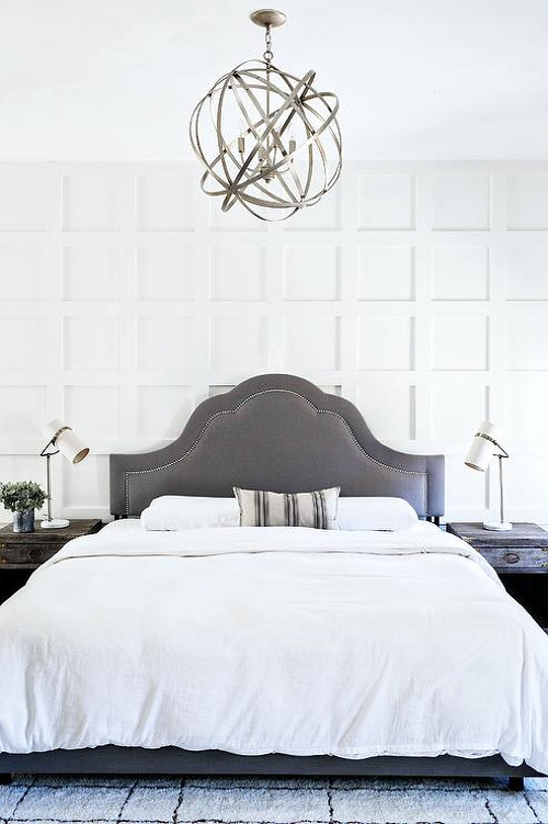 Bedroom with grey bed. Grey Bedroom. Sat against a board and batten wall, a dark gray linen curved headboard with a nailhead trim is dressed in a white duvet accented by a striped gray lumbar pillow. The bed is flanked by gray distressed nightstands with brass corners and topped with white adjustable lamps sat on a gray wool rug lit by a dark nickel sphere pendant light. #greybed #bed #bedroom Milk and Honey Home via Rue Magazine.