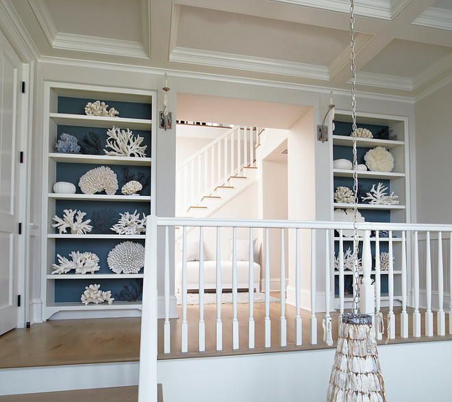 Built-in bookcases with wallpaper display a beautiful collection of white and blue corals. #Coral #bookcase #wallpaper TS Adams Studio Architects. Laura Allyson Interiors.