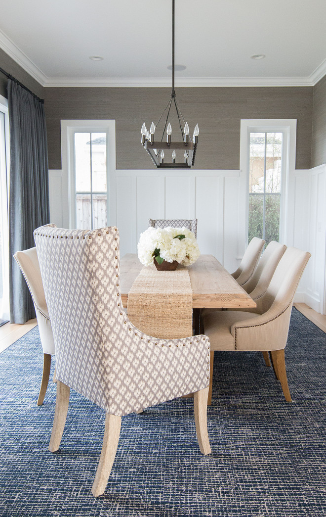 Dining room wainscoting. In this dining room, the designer added a slate blue gray grasscloth wallpaper above the wainscot that really adds an extra pop of color and richness to this room. #diningroom #wainscoting Blackband Design.