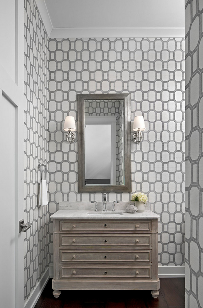 Geometric wallpaper. Geometric wallpaper Phillip Jeffries What a Gem Silver on White Manila Hemp wallpaper lines the walls of this stunning gray powder room boasting a French washstand topped with honed white marble countertops holding a sink fitted with a polished nickel faucet positioned under a gray beveled mirror flanked by polished nickel sconces, Jonathan 1 Light Sconces In Crystal with Natural Paper Shades. #geometric #wallpaper Marianne Jones LLC