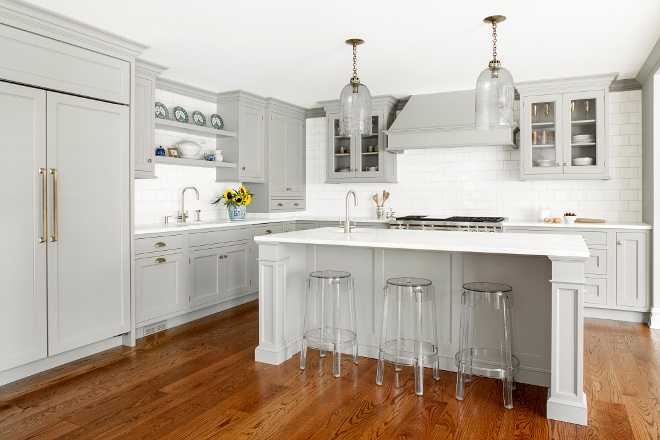 "Gray Kitchen. When Michelle and Dale approached Heidi Piron from Heidi Piron Design & Cabinetry about renovating the kitchen in their center hall Colonial in Summit, NJ, they wanted to open it into a family room and breakfast area. With three children -- a son in college, a daughter in high school and a son in middle school -- the household is a whirl of activity. As with the other more public spaces in the house, they wanted the kitchen to be quiet and minimal in feeling as a counterpoint to their busy, ""gear-and-stuff-filled lives,"" as Michelle described it. Michelle's design aesthetic is a blend of traditional and contemporary. She gravitates towards the antique and the artisanal, which Heidi incorporated in this custom gray kitchen. Heidi Piron Design & Cabinetry"