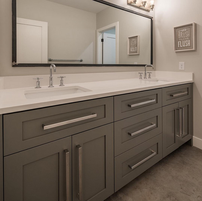 grey bathroom cabinet with white quartz countertop and concrete floors
