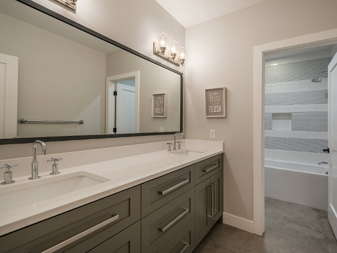Grey bathroom vanity, extra wide cabinet pulls, concrete flooring and white quartz countertop. Northstar Builders, Inc.