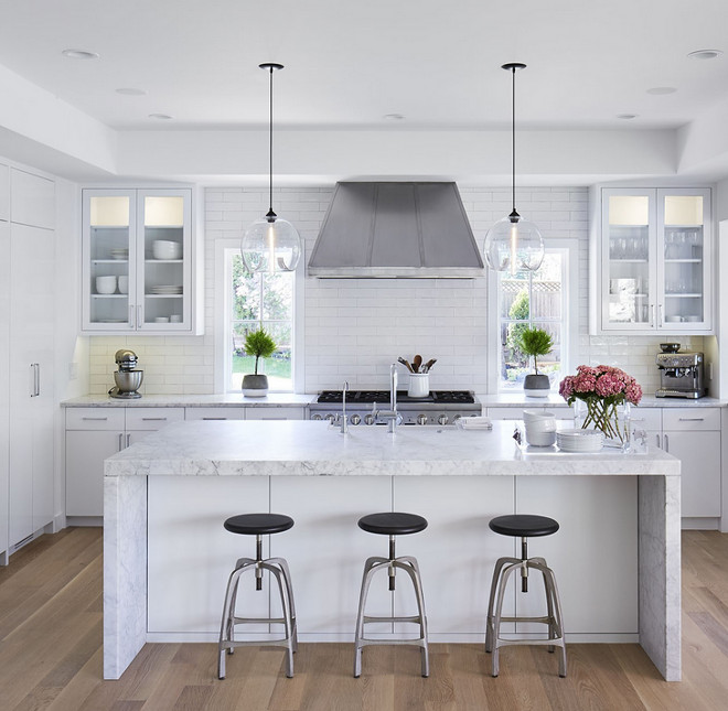 "Kitchen reno with white cabinets. White kitchen renovation ideas. The kitchen was completely renovated and it now feels bright and open. Cabinetry: Paint Grade Wood - Paint Color: ""Benjamin Moore Super White OC-152"" in a white lacquer finish. #whitekitchenreno #kitchenreno #whitekitchenrenovation #BenjaminMooreSuperWhite Martha O'Hara Interiors"