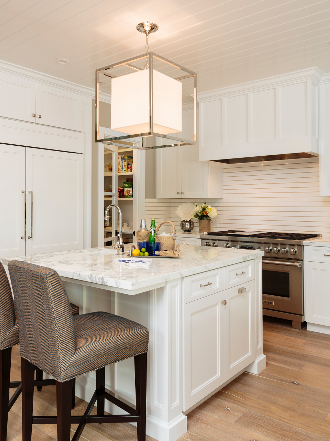 Kitchen. White kitchen. Fresh new white kitchen with island and light hardwood flooring. An intriguing backsplash tile resembles shiplap wainscoting. #kitchen #whitekitchen #white #kitchen Designed by Barclay Butera