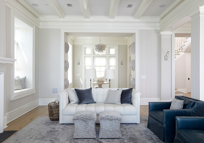Living room. Living room features an ivory coffered ceiling, with coffers painted white, accented with a modern brown ceiling fan creating a cool breeze over white tufted roll arm sofas lined with blue pillows facing each other across from an industrial coffee table. A pair of blue accent chairs face a white shiplap fireplace wall fitted with a flat panel tv over a white fireplace mantel finished with a black stone surround flanked by window seat alcoves. #livingroom TS Adams Studio Architects. Laura Allyson Interiors.