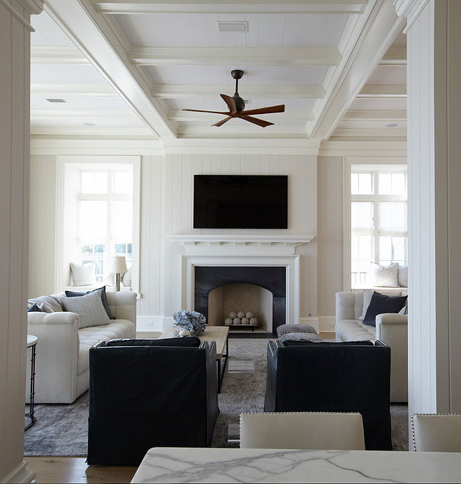 Living room coffered ceiling. The living room features an ivory coffered ceiling, with coffers painted in white accented with a modern wooden ceiling fan. A pair of blue accent chairs facing a shiplap fireplace wall fitted with a flat panel tv over a white fireplace mantel finished with a black stone surround flanked by window seat alcoves.#livingroom #cofferedceiling #tongueandgroove #paneledwalls.