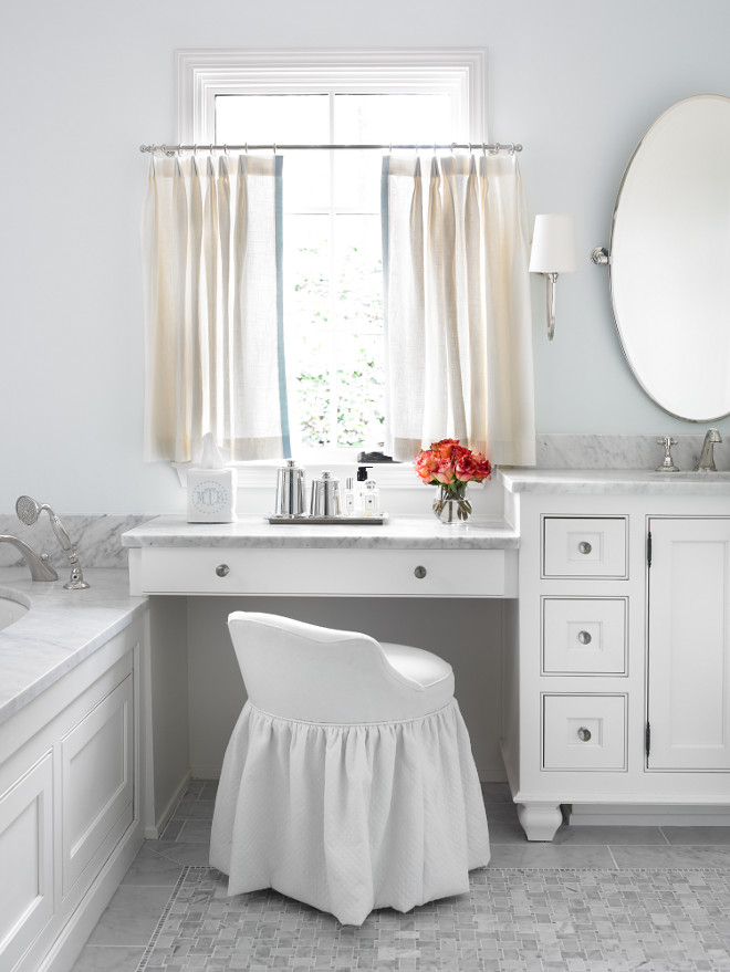 Make up vanity in bathroom. Bathroom with marble-top drop down make-up vanity under window covered in linen cafe curtains paired with white slipcovered vanity stool. White bathroom cabinets with carrara marble countertops and oval pivot mirror accented with monogrammed embroidered tissue box cover. Master bathroom features wood paneled drop-in tub with carrara marble surround over carrara marble mosaic tile floor. L. Kae Interiors