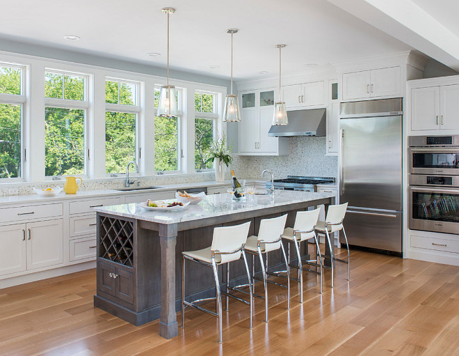 "Kitchen. This kitchen feels open and airy. The wall paint color is C-2 Seraph. Trim paint color (for whole house) is ""Benjamin Moore OC-67 Ice Mist"". Cabinets: Cabinets are White Inset Starmark - White Inset DeWitt Door. Island: Island is Starmark Gray Stain with Pewter Glaze. #kitchen #openkitchen #airykitchen #kitchenpaintcolor Caldwell & Johnson Custom Builders & Remodelers"