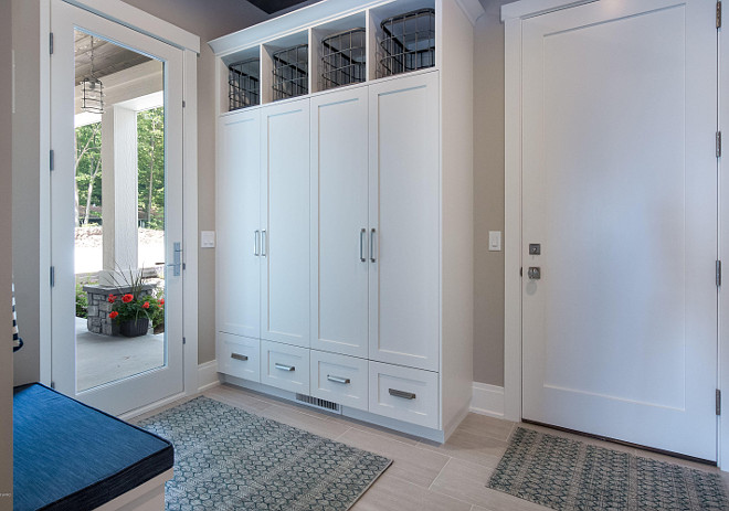 Mudroom. Garage door opens to a mudroom with tile floors, closed cubbies with doors and a small built-in bench. #mudroom #door #cubbies #floortile #tile