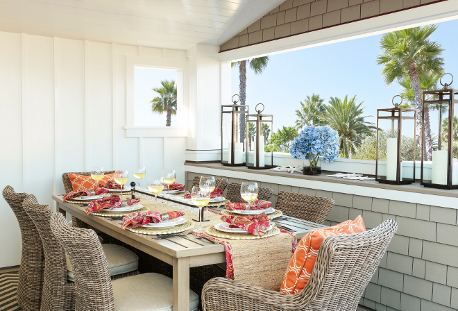 Outdoor dining area. How to decorate outdoor dining areas - furniture, tabletop, decor, rug. In this outdoor area, happy colors play beautifully against classic architectural elements such as shingles and board and batten walls. Designed by interior designer Barclay Butera.