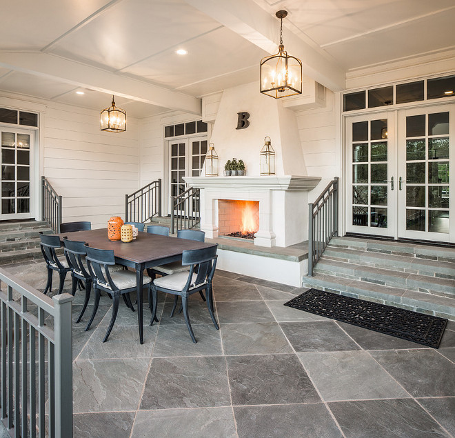 Porch fireplace and slate floor tile. Beautiful porch fireplace, slate floor tile and vaulted ceilings with lantern pendant lights. #porch #fireplace #slatefloortile #floortile #tile #vaultedceiling Fox Group Construction