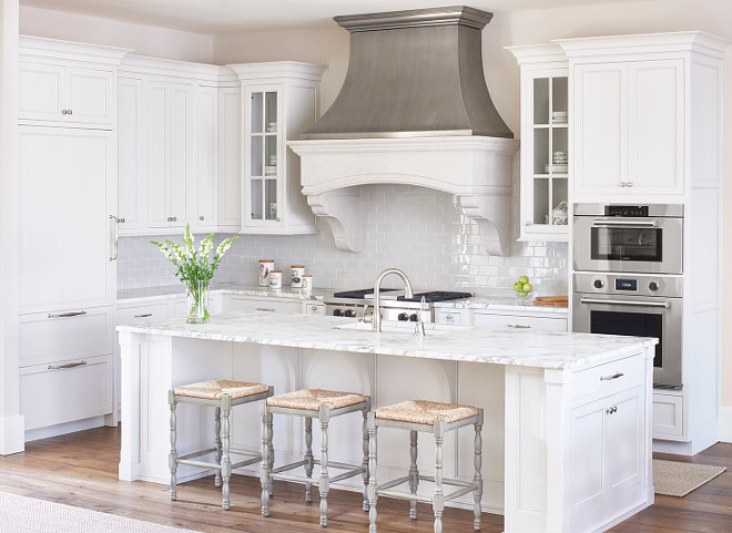 White and pale gray kitchen. White and gray kitchen features a white center island topped with gray and white marble fitted with a white porcelain sink and a satin nickel gooseneck faucet lined with gray backless counter stools with rush seats. A zinc French kitchen hood with corbels stands over a gray mini subway tile backsplash and a stainless steel stove. #whitekitchen #palegraykitchen #graykitchen #kitchen  L. Kae Interiors