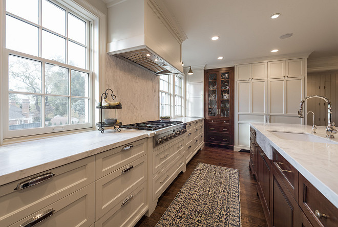 White kitchen cabinets with walnut kitchen island and oak floors. Northstar Builders, Inc.