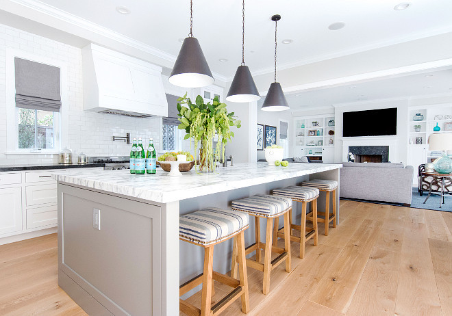 White kitchen with pale grey island and striped barstools. California style White kitchen with pale grey island and striped barstools. #Whitekitchen #palegreyisland #stripedbarstools Graystone Custom Builders. Blackband Design.