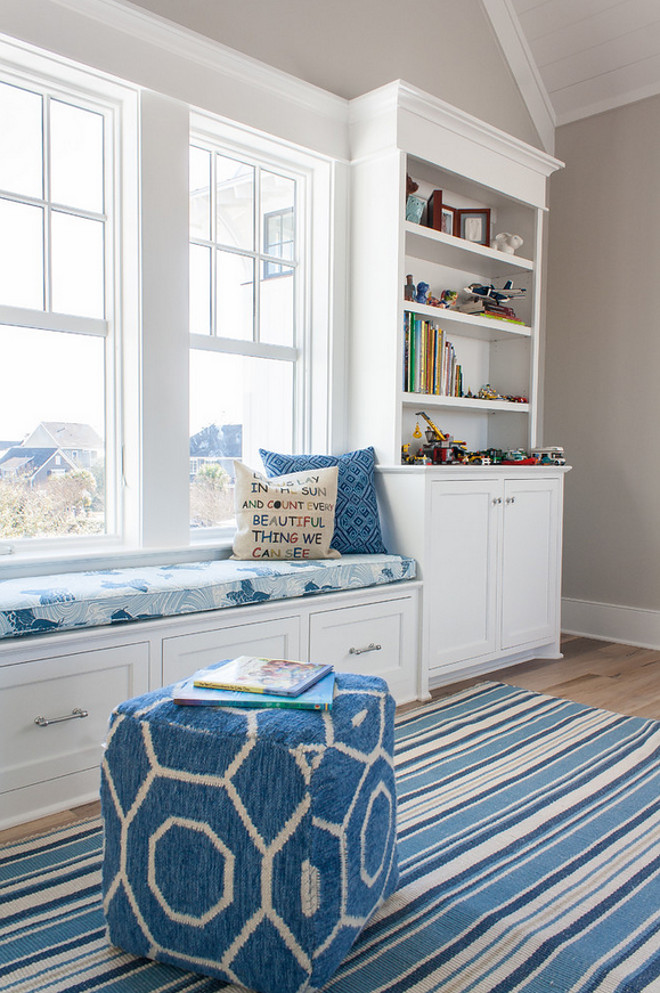Window seat flanked by built-in cabinets with bookcases, blue striped rug and blue and white ottoman and pillows. Cabinet paint color is Sherwin Williams SW7006 Extra White. The Guest House Studio