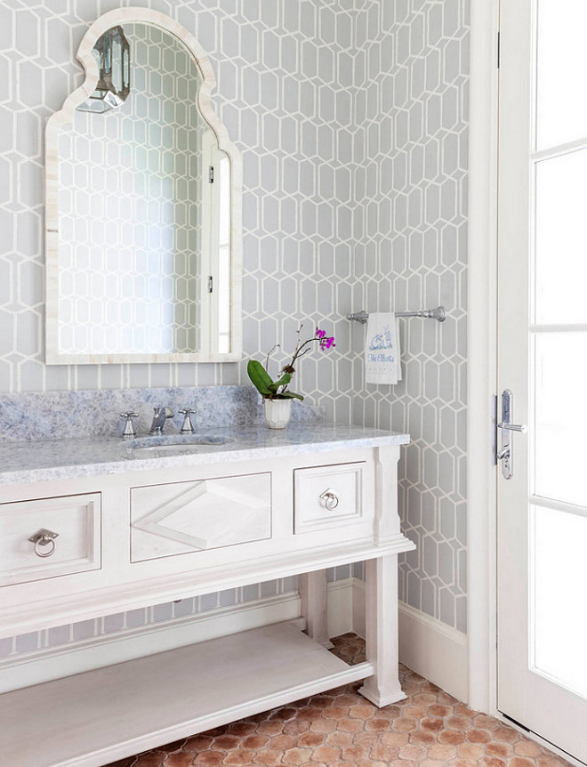 Bathroom. Bathroom features white washstand cabinet style, grey geometric wallpaper and terracotta floor tiles. #Bathroom #whitecabinet #terracotta #tile #greygeometricwallpaper Robert Elliott Custom Homes