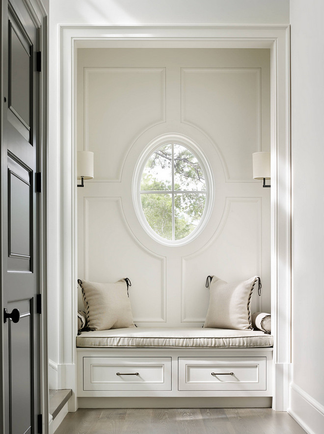 Benjamin Moore Sheeps Wool. Benjamin Moore Sheeps Wool. Foyer features a nook with a built-in window seat with drawers illuminated by Barbara Barry's sconces next to staircase and grey front door. Wall paint color is Benjamin Moore Sheeps Wool. #BenjaminMooreSheepsWool Beth Webb Interiors