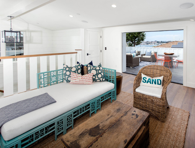 Coastal family room with reclaimed wood table, wicker chair, jute rug and turquoise daybed. Blackband Design