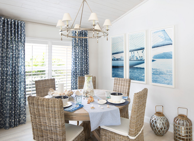 Dining area with rattan dining chairs, reclaimed wood ceiling, coastal wall art and navy draperies. #diningarea #rattanchairs #diningchairs ##woodceiling #reclaimedwoodceiling