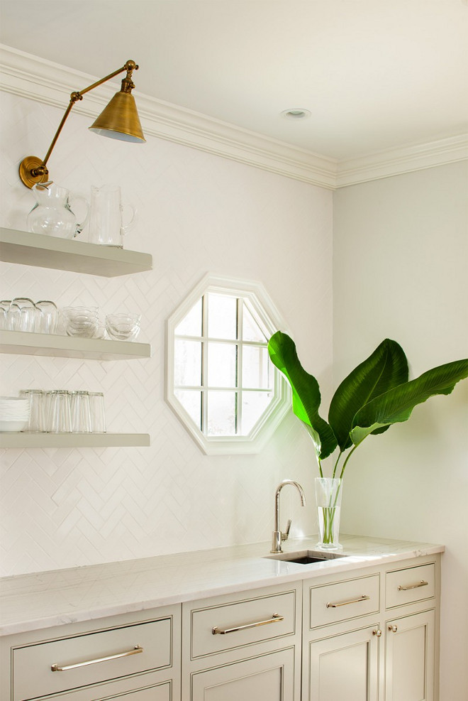 Floating open shelves. Pale Gray Floating Open Shelves. Floating pale gray shelves are lit by Boston Functional LIbrary Wall Lights mounted on white chevron backsplash tiles framing an octagon window located over a small prep sink fitted with a polished nickel gooseneck faucet fixed in Bianco Macabus Quartzite countertops positioned atop gray shaker cabinets finished with polished nickel pulls. #palegray #openshelves #floatingshelves Revival Construction