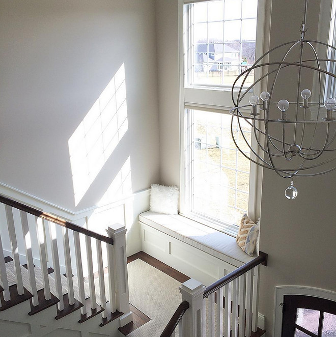 Foyer Orb lighting and stair window seat. Paint Color is Sherwin Williams SW7036 Accessible Beige. Orb chandelier in foyer. Orb chandelier is from Ballard Designs. #SherwinWilliams #SW7036 #AccessibleBeige Beautiful Homes of Instagram carolineondesign