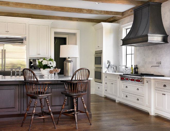French country kitchen. French Country kitchen. French country kitchen with zinc French kitchen hood with swing-arm pot filler over integrated Wolf Range. Two-tone kitchen features white shaker perimeter cabinets with marble tile backsplash and chocolate brown kitchen island with sink lined with vintage windsor bar stools over warm wood floors. Rustic kitchen with exposed wood beams, double ovens and counter depth double door refrigerator #frenchkitchen #FrenchCountry #FrenchCountryKitchen L. Kae Interiors
