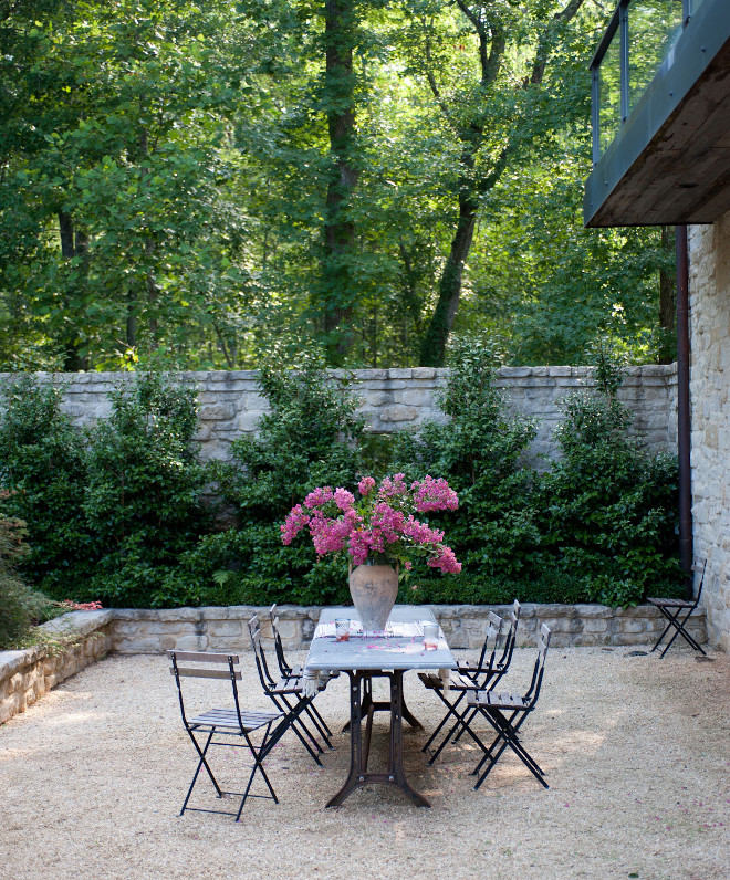 Gravel Patio. French style gravel patio with stone garden walls. Gravel patio with French bistro table in iron and marble lined with delicate slatted wood outdoor dining chairs . #Gravel #patio #FrenchGardens #Gardens #Garden #Stonewall Smith Hanes