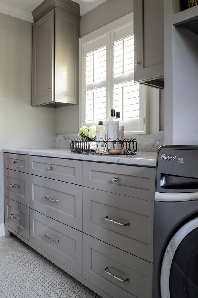Laundry room Gray,cabinets, in,laundry,room, open,shelves,for, basket,storage,and,organization, organize,carrara,marble, counter, and,splash,hex,tile,floor,ceramic,vintage,look,ceiling,light. Laundry room with Carrara marble countertop. BRADSHAW DESIGNS LLC