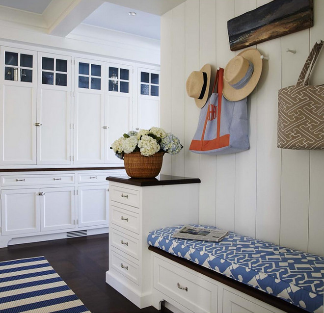 Mudroom. Classic coastal mudroom with white cabinets, blue and white bench fabric, shiplap walls and dark stained hardwood floors. Mudroom #Mudroom #Classiccoastal #coastalmudroom #whitecabinets #blueandwhite #bench #fabric #shiplap #darkstainedfloors #hardwoodfloors Lynn Morgan Design.