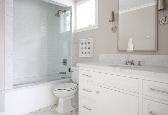 "Bathroom tub. Guest Bath Tub: Marble slab surrounds with tub tob, wood accent front panel and 2x4 white hand pressed subway tile. Sconces are from ""Restoration Hardware Modern"". Winkle Custom Homes. Melissa Morgan Design. Ryan Garvin Photography"