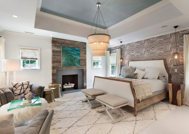 Master Bedroom. Transitional Master Bedroom. The bed chamber features a high tray ceiling and a fireplace with a surround comprised of natural stone and floor to ceiling antique Vermont barn board siding. #Masterbedroom #transitionalmasterbedroom #transitionalbedroom Bluewater Home Builders