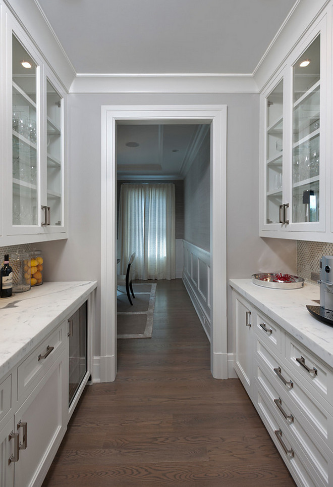 Butlers pantry by dining room. The formal dining room with paneling and tray ceiling is serviced by a custom fitted double-sided butler's pantry with hammered polished nickel sink and beverage center. #butlerspantry #diningroom #countertop #beveragecenter Bluewater Home Buildersutlers-pantry